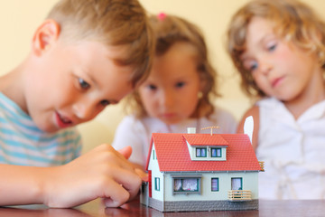 children three together looking at model of house
