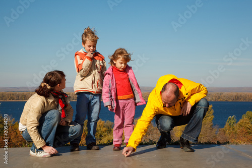 Family walks in solar autumn day. Parents draw chalk on asphalt.