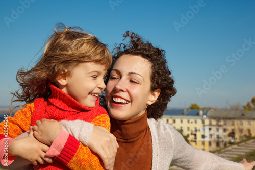 Mother and daughter outdoors. They laugh sunny autumn day.