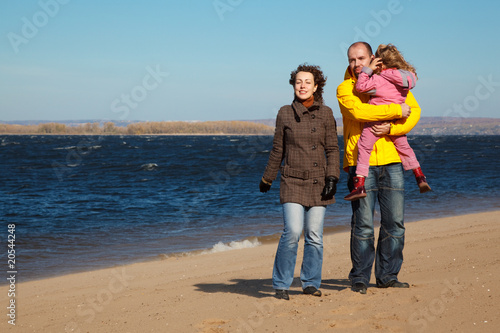 Parents with little girl walk on autumn beach.