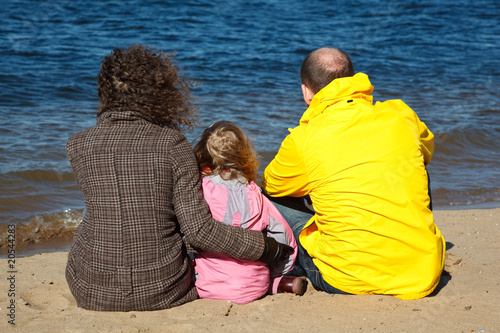 Family of three people sitting on sand on river bank.