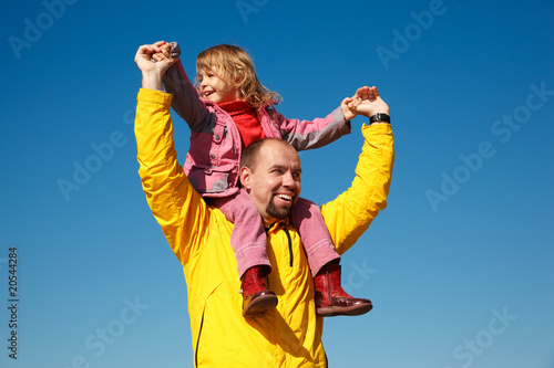 Cheerful little girl sits on shoulders at man, against blue sky.