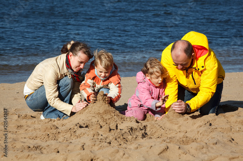Boy and girl with their parents play in sand on beach