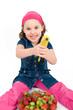 Mädchen mit Banane vor einer Obstschale