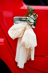 Bow with flowers on door handle of red wedding limo