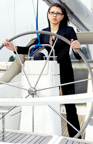 Beautiful sexy brunette stands after a steering wheel on a ship
