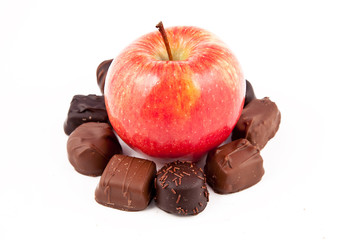 Red Apple and chocolate pieces surrounding it