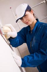 Young woman builder polishing the wall