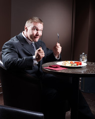 Muscular businessman in suit smiling and eating