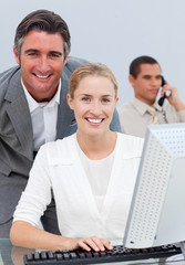 Confident business team working at a computer