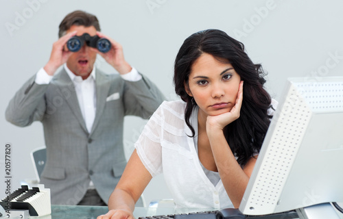 Brunette businesswoman annoyed by a man looking through binocula