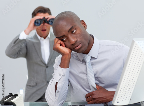Afro-american businessman annoyed by a man looking through binoc