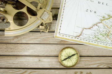 old map sextant and compass on wood background