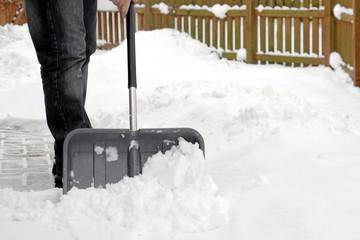 Mann beim Schnee schieben