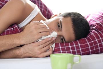 Jugendlicher mit Erkältung im Bett