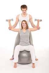 Fitness - Young couple training with weights and ball