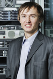 Portrait of young data center specialist in front of equipment poster