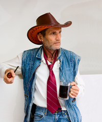 Man in cowboy hat with mug and pipe