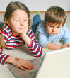 Kinder liegen vor Laptop