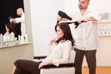 Professional hairdresser with hair dryer at salon with customer poster