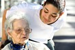 jeune soignante assistant une personne agée