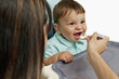 Young woman feeding baby boy in high chair