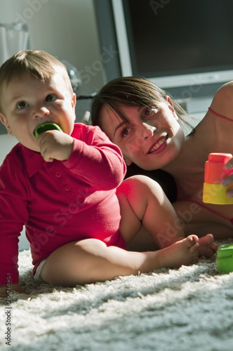 Young woman and baby boy sitting on rug chewing on and playing with toys