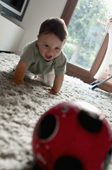 Baby boy crawling toward ball