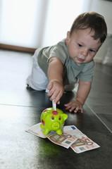 Baby boy putting money in the piggy bank