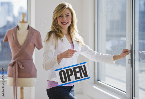 Shopkeeper holding open sign - 20626610