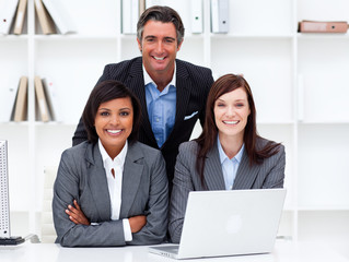 Enthusiastic businesswomen and their colleague working at a lapt