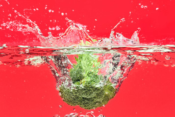 Green broccoli falling in water with air bubbles