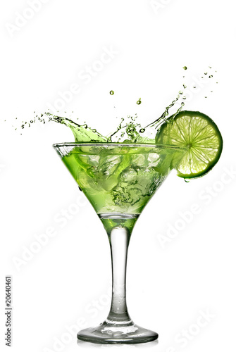 Green alcohol cocktail with splash and green lime isolated