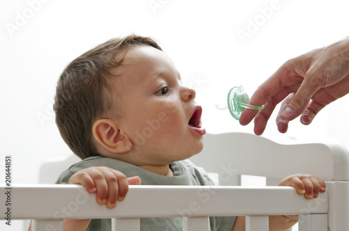 Baby boy with female hand giving pacifier
