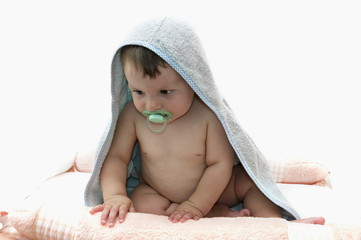 Baby boy wrapped in towel with pacifier