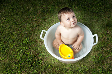 Baby boy taking bath in tub in garden