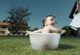 Baby boy taking bath in tub in garden and partial view of young woman with towel