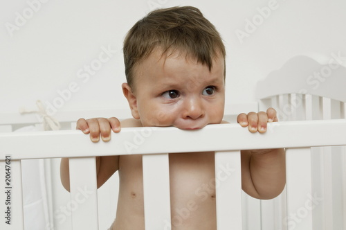 Baby boy in crib chewing on rail