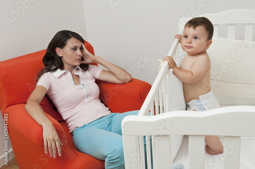 Young woman on arm chair holding her head and baby boy in crib