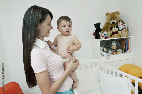 Young woman holding baby boy in bedroom