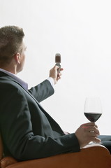 Young man in business suit sitting with glass of red wine and mobile phone