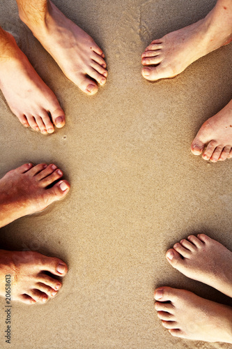 feet of family, father, mother  and two suns at the sandy beach