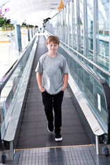 boy in the departure hall  in the  Airport on a moving staircase