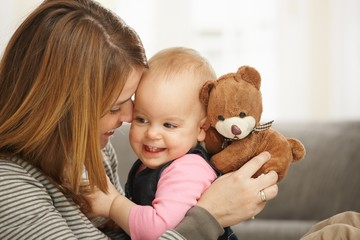 Happy mum and baby with teddy bear