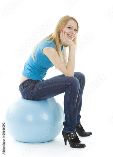 smiling girl on blue ball isolated on white