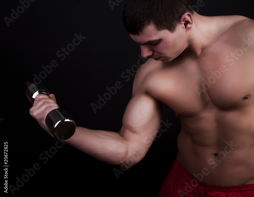 Handsome man holding dumbbells