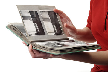 Woman looking in old photo album with b/w photos
