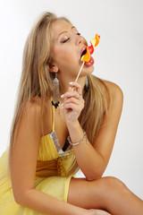 Sexy young woman sucks  sugar candy