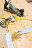 Safety glasses, smoothing plane, carpenters square on desktop
