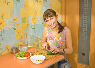 The woman prepares salad and vegetables